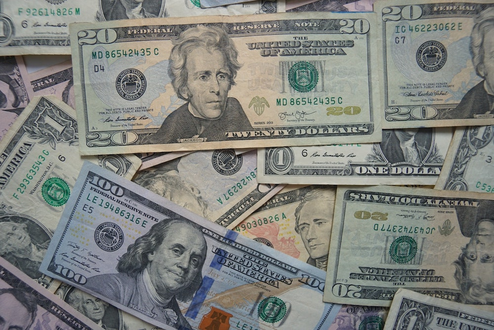 Close up of a disheveled pile of cash mixed together with different bills ranging from 1 to 100