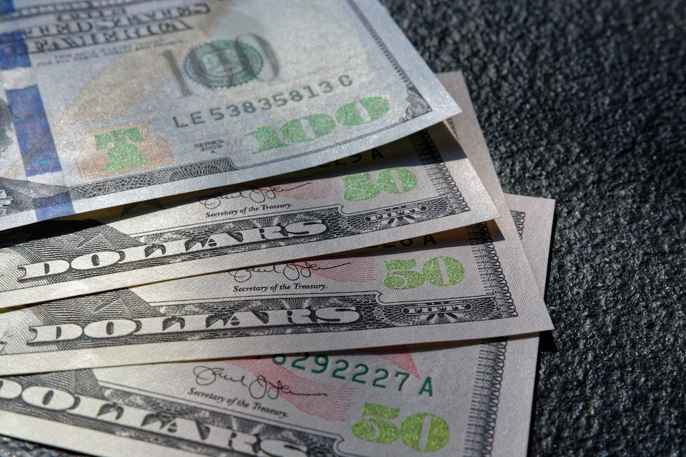 A close up of one 100 and three 50 dollar bills fanned out on a rough black surface