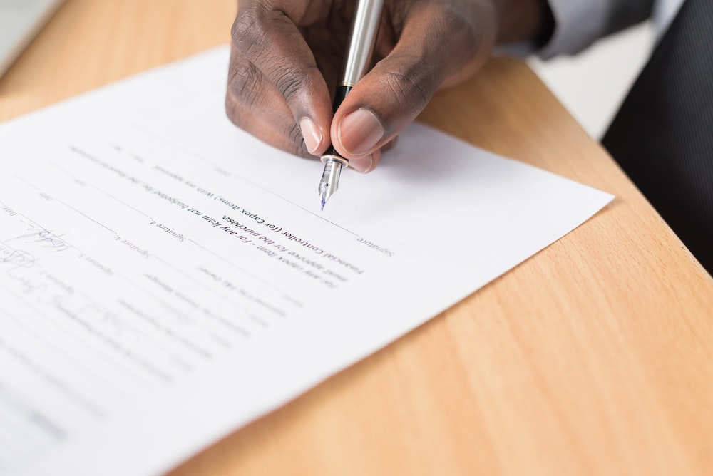 A close up of a man's hand signing legal paperwork at a wood table