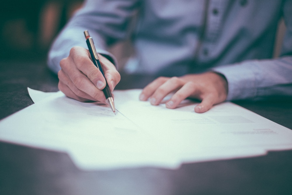 A man in a blue business shirt signing a stack of three of papers on a wood table
