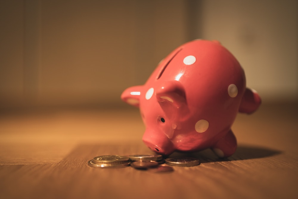 A small pink piggy bank with white polka dots tipped over on a wood floor with coins spilled out