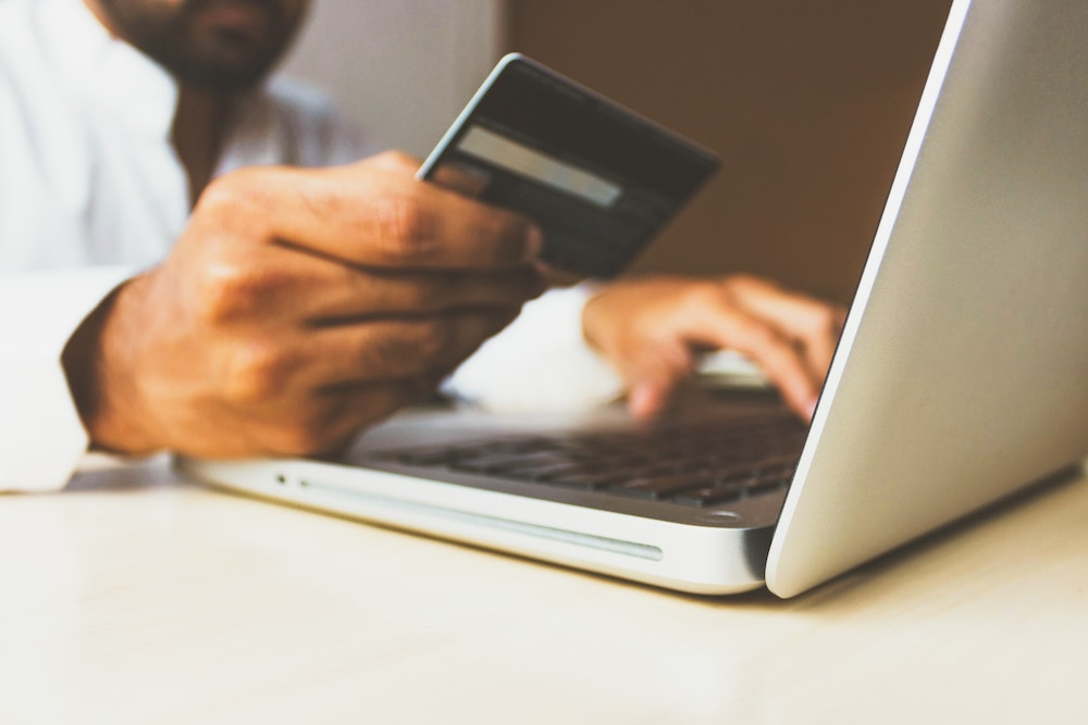 A close up of a man on his laptop holding up his credit card and typing in the numbers
