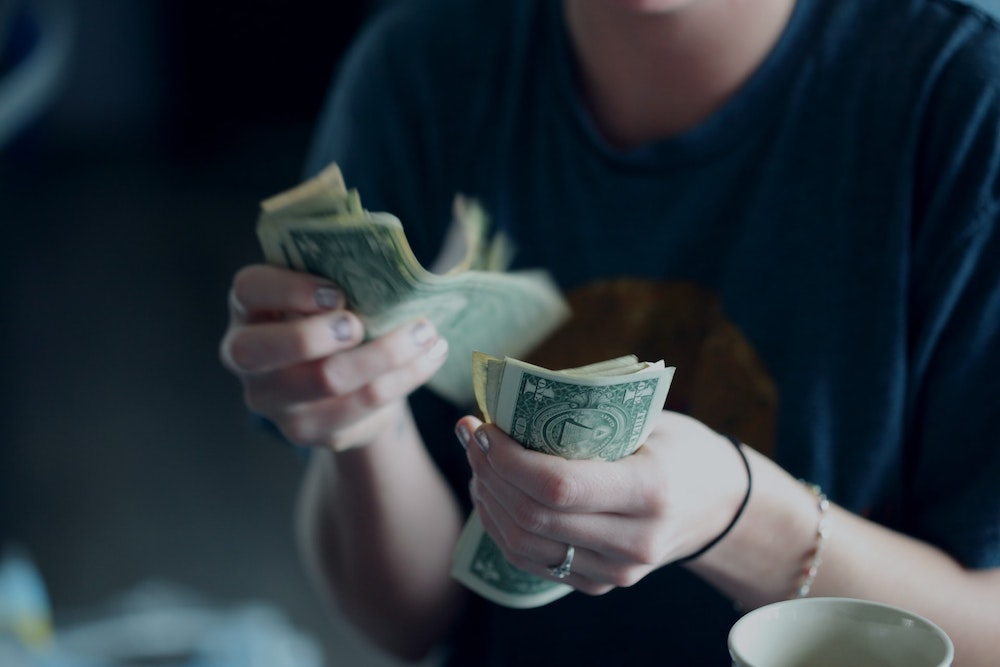 A woman wearing a blue shirt holding a stack of dollars bills and counting them from one hand to the other