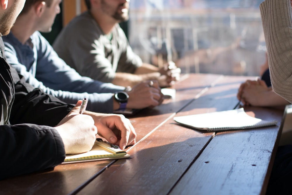Four people sitting around a wooden office table with notepads and pens taking notes on a business meeting