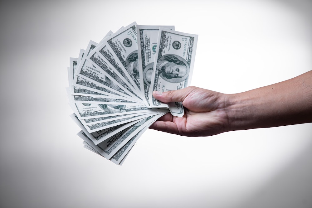 A hand holding out fifteen hundred dollar bills fanned out on a white background with shadows in the corners